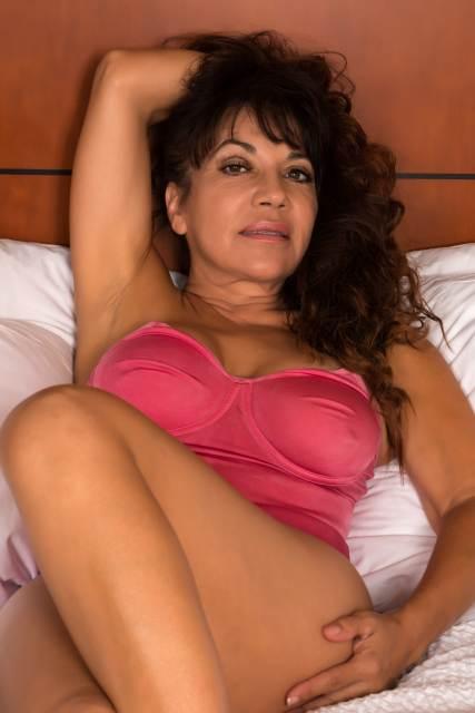 Frau räkelt sich für Kamra auf Bett