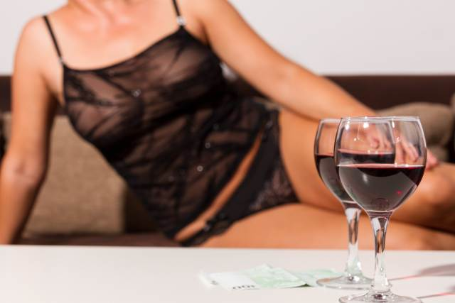im Vordergrund stehen zwei gefüllte Rotweingläser, im Hintergrund liegt Frau in schwarzer Reizwäsche