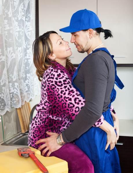 Frau in pinkem Leopardenmantel schmiegt sich eng an Handwerker