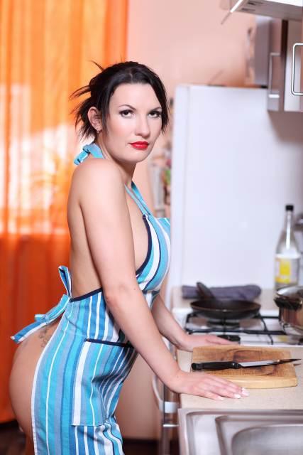 Frau steht nur mit Kittelschürze bekleidet in Küche