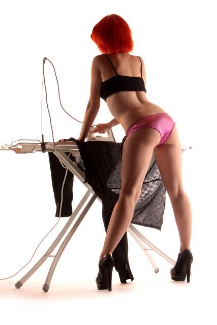 Rückansicht von Frau in Reizwäsche, die am Bügelbrett steht