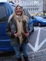 Frau in Winterkleidung steht auf Parkplatz