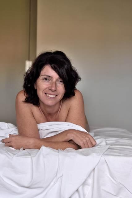 brünette Frau liegt auf Bett