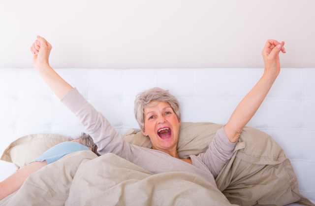 ältere Frau räkelt sich nach dem Aufwachen