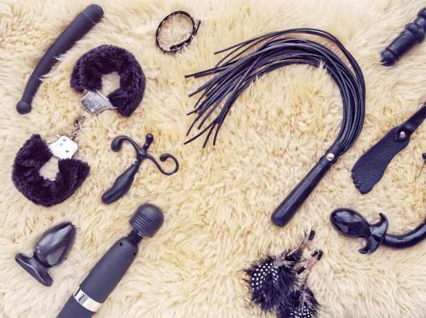 Auswahl an schwarzen Sextoys auf weißem Flokati Teppich