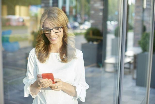 Attraktive ältere Frau lächelnd am Smartphone