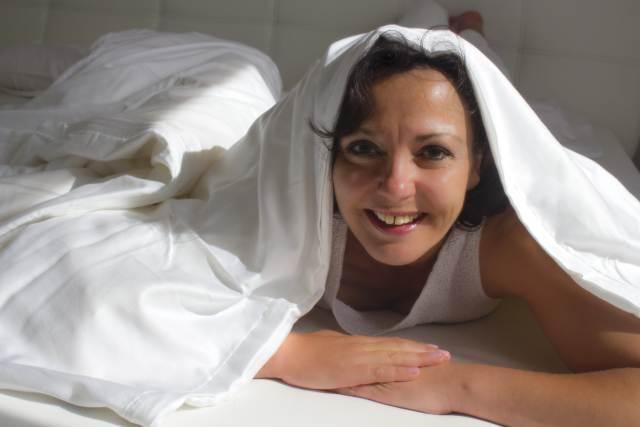 Attraktive Frau mittleren Alters schaut unter einer Bettdecke hervor