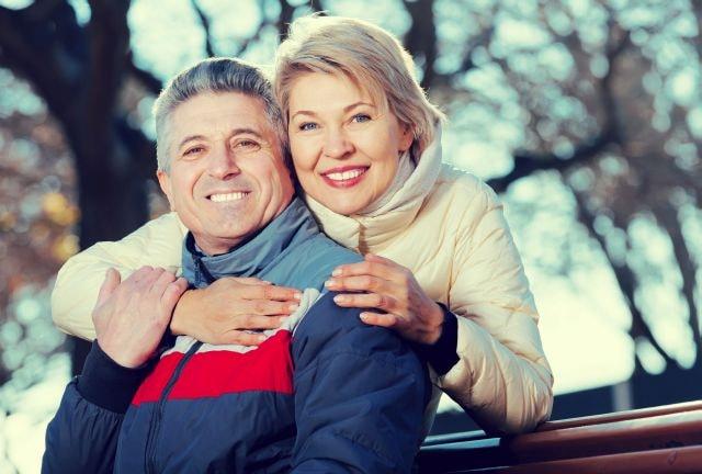 Attraktives älteres Paar lächelnd draußen
