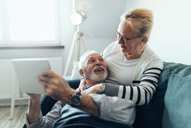 lächelndes altes Paar auf dem Sofa mit Tablet