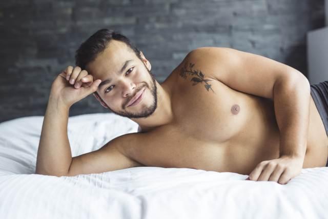 junger Mann posiert halbnackt auf Bett