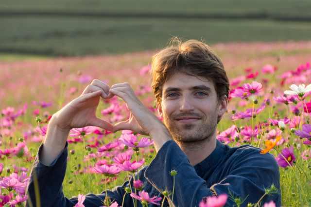 junger Mann sitzt auf einer Blumenwiese, zeigt Herzsymbol mit beiden Händen