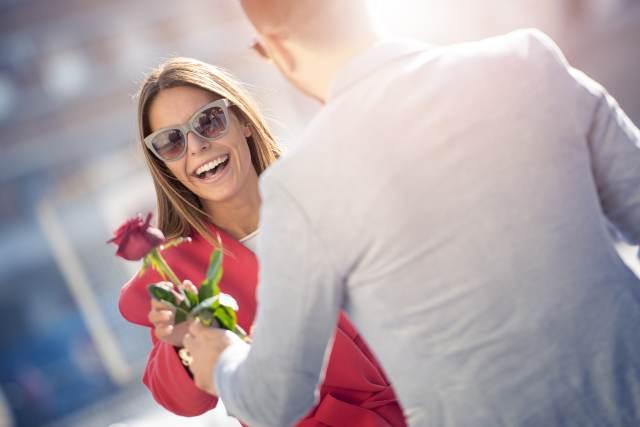 Mann überreicht Frau eine Rose