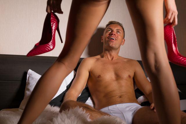 Mann liegt im Bett, vor ihm steht seine Freundin mit High Heels in den Händen