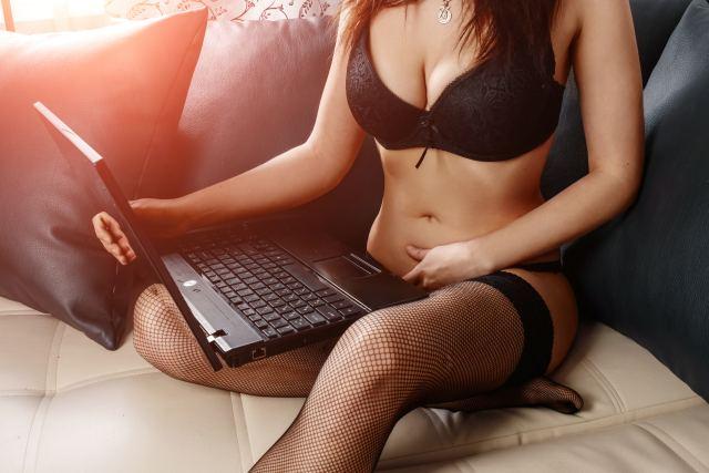 Frau in Reizwäsche mit Laptop auf dem Schoß