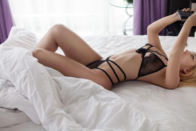 Frau liegt in Reizwäsche auf Bett und schaut auf ihr Smartphone