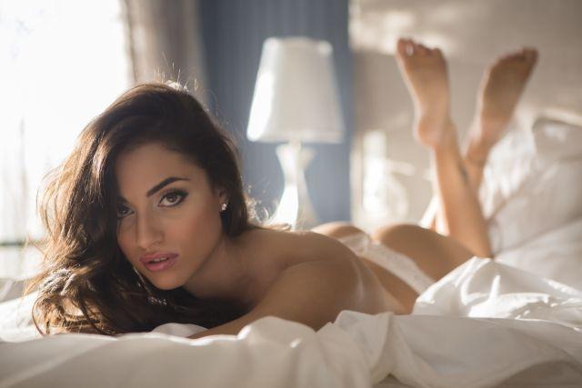 Attraktive dunkelhaarige Frau posiert auf dem Bett