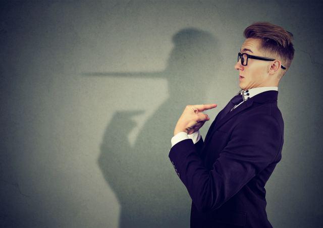 Mann zeigt auf sich, sein Schatten zeigt eine Pinocchio-Nase
