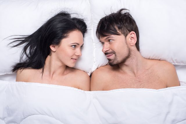 Paar liegt im Bett und schaut sich lächelnd an