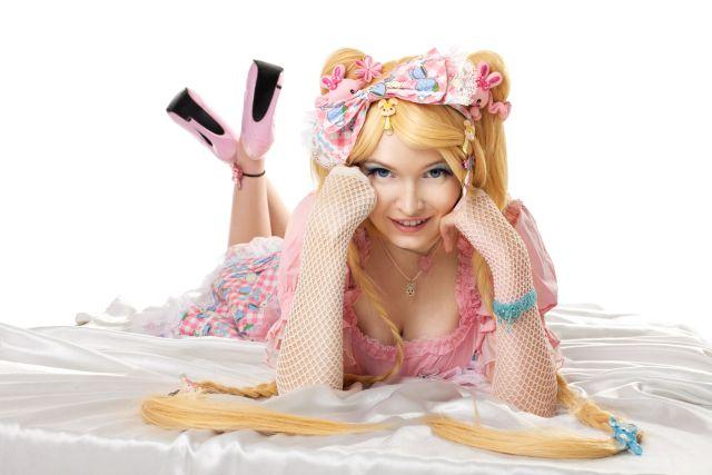 Frau liegt in rosa Kostüm auf Bett