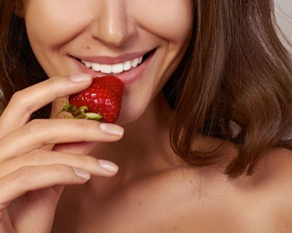 Frau führt Erdbeere zum Mund
