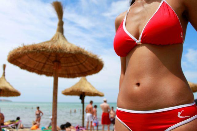 Frau im roten Bikini am Strand