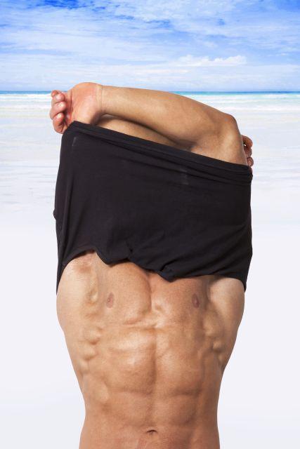 Mann zieht sch am Strand das T-Shirt aus