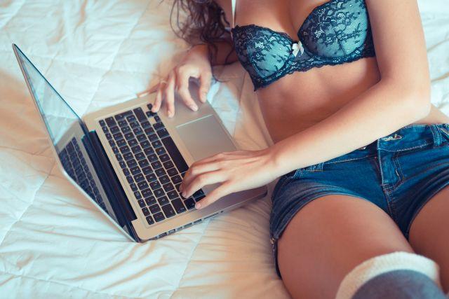 Frau in Dessous liegt mit Laptop im Bett