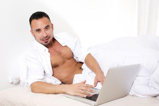 Attraktiver Mann mit Laptop im Bett