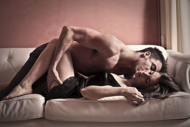 Paar liegt eng umschlungen auf Sofa