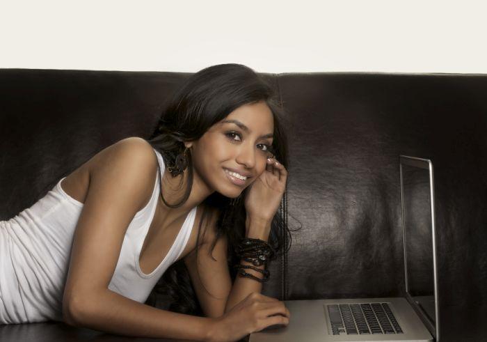 Frau liegt mit Laptop auf Sofa