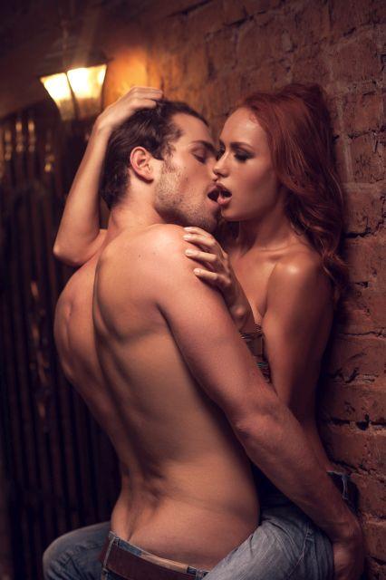 Nacktes Paar umschlingt sich im Stehen an der Wand