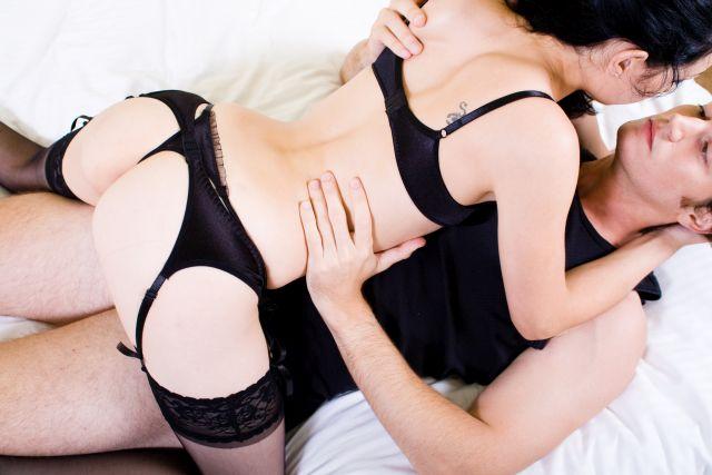 Paar liegt umschlungen auf Bett