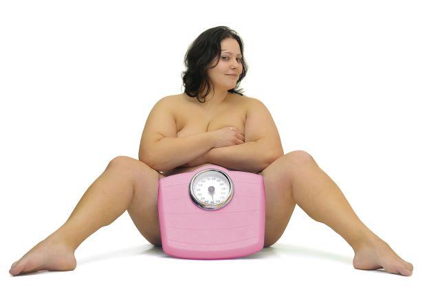 Stark übergewichtige, nackte Frau hat eine Körperwaage zwischen ihren gespreizten Beinen stehen