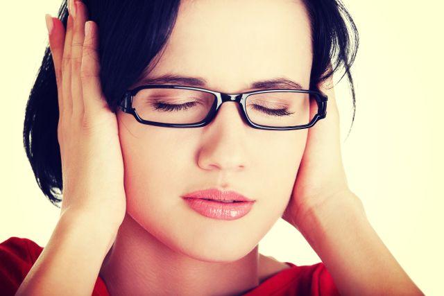 Dunkelhaarige Frau mit Brille hält sich die Ohren zu...
