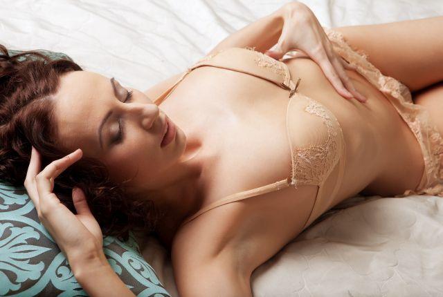 Leidenschaftliche Frau in Unterwäsche auf dem Bett