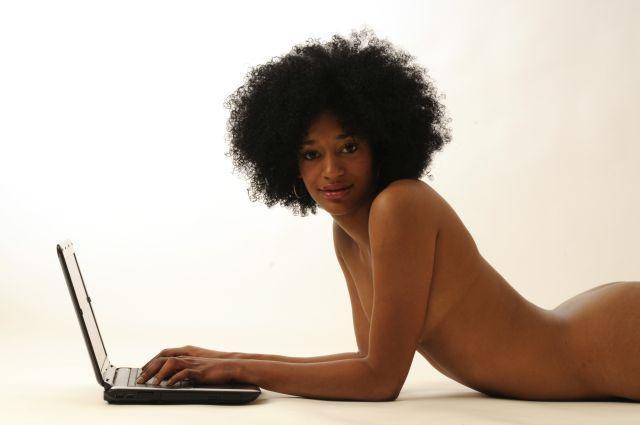 Schwarze Frau liegt nackt vorm Laptop