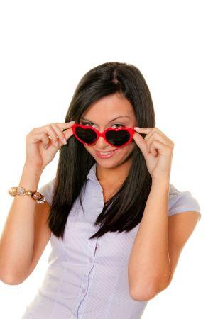 Dunkelhaarige Frau mit roter Herzchen-Sonnenbrille