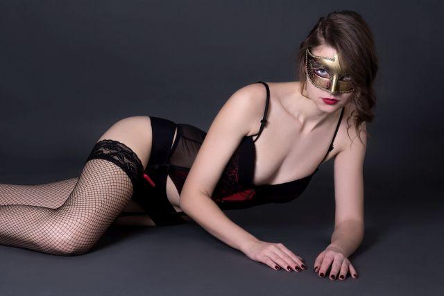 Frau mit goldener Maske und schwarzen Dessous liegt provokativ auf dem Boden.