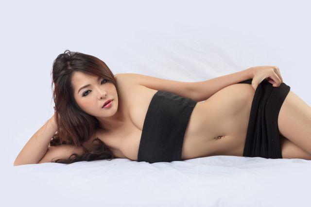 Knapp bekleidete asiatische Frau posiert auf dem Bett