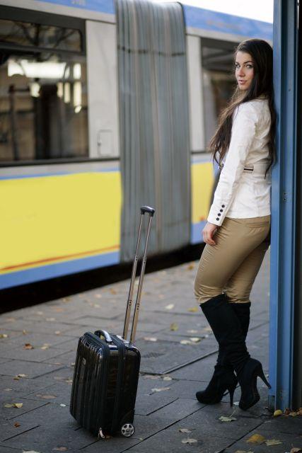 Frau steht wartend an Bushaltestelle