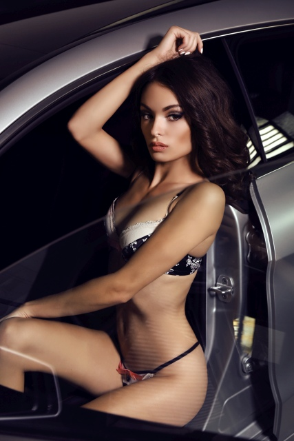 Sexy Frau posiert in Dessous in einem Auto