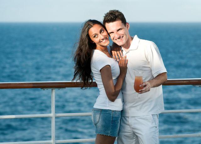 Junges Paar steht an der Rehling eines Schiffes. Im Hintergrund ist das blaue Meer zu sehen.
