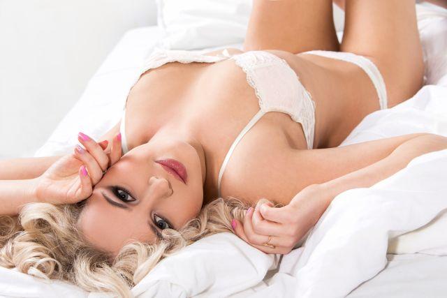 Blonde attraktive Frau in weißer Unterwäsche