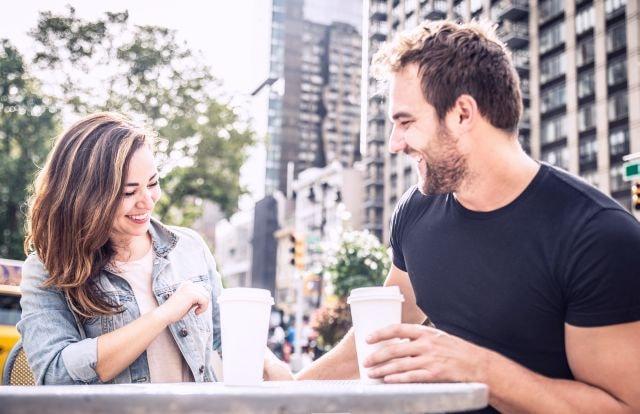 Paar sitzt draußen mit einem Kaffee
