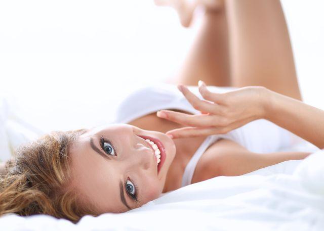 Junge schöne Frau liegt im Bett