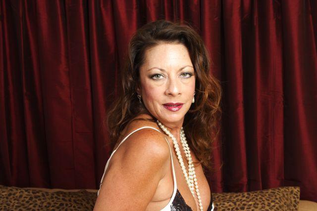 Reife Frau mit Perlenkette schuat lasziv in die Kamera