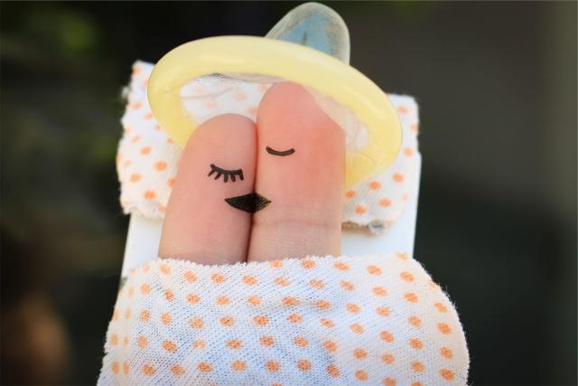 Zwei Finger mit aufgemalten Gesichtern küssen sich unter einem Kondomhut
