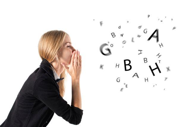 Blonde Frau redet während Buchstaben aus ihrem Mund kommen
