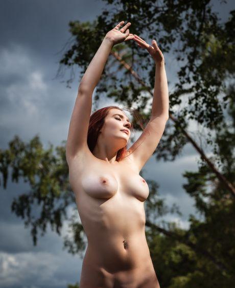 Nackte rothaarige Frau posiert in der Natur