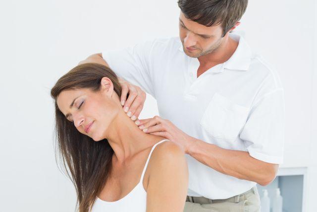 Arzt massiert Frau am Nacken